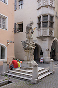 Tourists sit beneath the St. John of Nepomuk monument in front of the Town Hall in Sterzing-Vipiteno, South Tyrol, northern Italy.