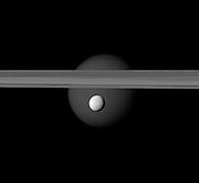 The brightly reflective moon Enceladus appears before Saturn's rings while the larger moon Titan looms in the distance.