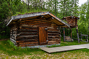 """Jack London's Cabin replica in Dawson City, Yukon, Canada. Jack London (1876–1916) was an American novelist, journalist, and social activist. At age 21, he spent a difficult winter 1897–1898 prospecting for gold from in a rented cabin on the North Fork of Henderson Creek, 120 km south of Dawson City, just prior to the gold rush of 1898. While he didn't strike it rich, he later turned his Klondike adventures into fame and fortune with legendary short stories and books. His most famous works include """"The Call of the Wild"""" and """"White Fang"""", both set during the Klondike Gold Rush. A pioneer in the world of commercial magazine fiction, he was one of the first writers to become a worldwide celebrity and earn a fortune from writing. He was also an innovator in the genre that would later become known as science fiction. Born as John Griffith Chaney, his last name become London through his mother's remarriage during his first year of life. He began calling himself Jack as a boy. London's cabin, abandoned after the Gold Rush, was re-discovered by trappers in 1936 who noted London's signature on the back wall. Yukon author Dick North organized a search in 1965 and eventually had the cabin dismantled and shipped out. Two replicas were made from the original logs. One is shown here in Dawson City, while the other was re-assembled at Jack London Square in Oakland, California, London's hometown."""