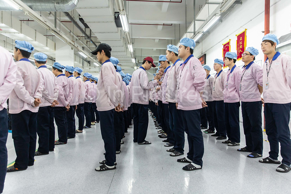 Employees line up for row call before their shift starts at a Pegatron Corp. factory in Shanghai, China, on Friday, April 15, 2016. This is the realm in which the worlds most profitable smartphones are made, part of Apple Inc.s closely guarded supply chain.