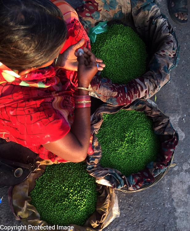 A woman sells peas from the sidewalk in Varanasi, India.<br /> Photo by Shmuel Thaler <br /> shmuel_thaler@yahoo.com www.shmuelthaler.com