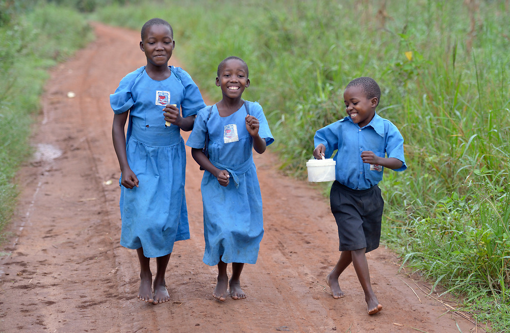 Children laugh and play as they walk to school in the morning in Lukaya, Uganda, where the Good Samaritan Women's Project has helped rural women improve their financial literacy, thus improving the quality of life for the women, many of whom are widows who also care for children who lost their parents to AIDS. The program was funded by the Call to Prayer and Self-Denial of United Methodist Women. These children are part of an extended family, where a widow with three children has adopted the four children of her sister who died.