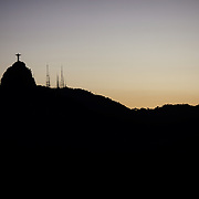 The iconic Cristo Redentor, Christ the Redeemer statue at sunset with communication antenna atop the mountain Corcovado shot from Suger Loaf Mountain. The Christ statue was voted one of the seven wonders of the modern world in 2007. It was designed by Brazilian Heitor de Silva Costa and was inaugurated in 1931 having taken years to assemble. Rio de Janeiro, Brazil. 21st July 2010. Photo Tim Clayton....