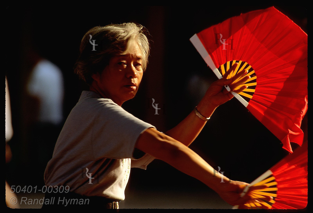 Silver-haired woman fan dances at sunrise in Jin An Park in central Shanghai. China