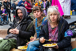 Protesters enjoy free vegan food as hundreds of environmental protesters from Extinction Rebellion occupy Oxford Circus, a pink yacht being the focal point of their presence, with traffic denied access to two of London's busiest streets. London, April 16 2019.