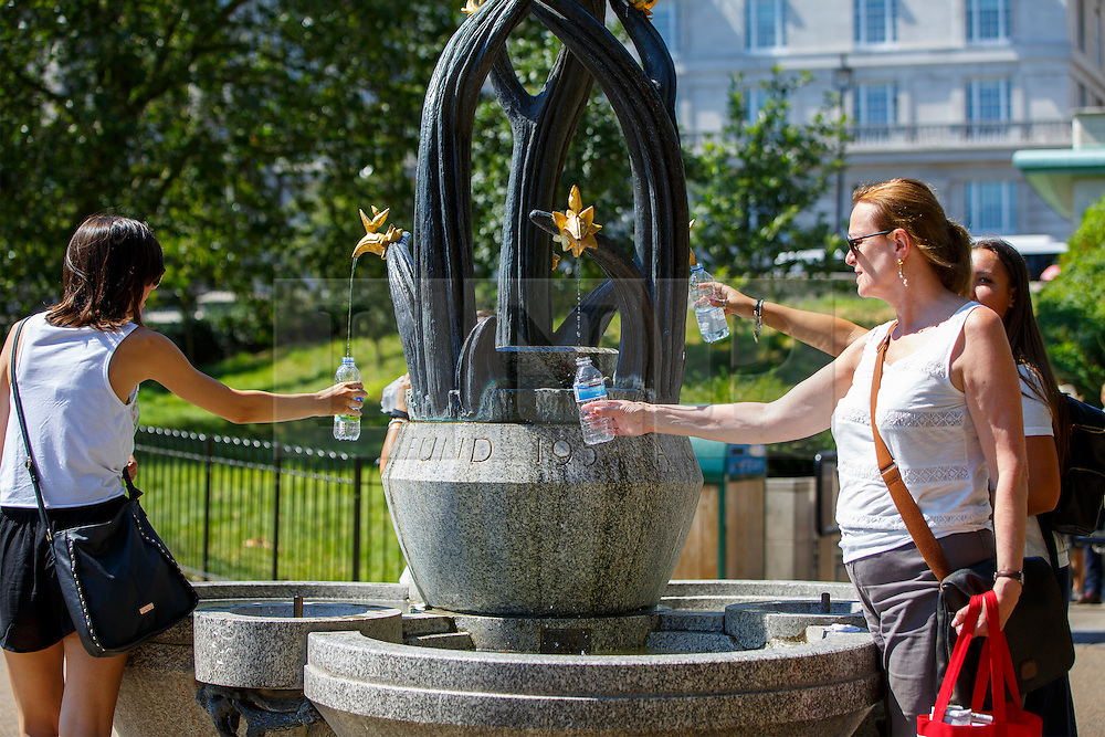 © Licensed to London News Pictures. 19/07/2016. London, UK. People fill their water bottles from a water fountain as they enjoy the hottest day of the year so far in the UK in Green Park, London on Tuesday, 19 July 2016. Photo credit: Tolga Akmen/LNP