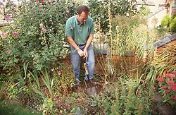 Man working in garden digging soil with spade,