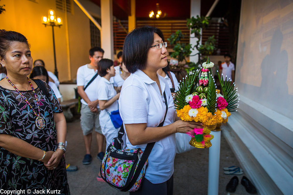 27 JANUARY 2013 - BANGKOK, THAILAND: A woman brings an offering of flowers to a shrine for Thaipusam at Dhevasathan (the Brahmin Shrines) on Dinso Rd in Bangkok. Thaipusam is a Hindu festival celebrated primarily by the Tamil community in South East Asia on the full moon in the Tamil month of Thai (Jan/Feb). Pusam refers to a star that is at its highest point during the festival. The festival commemorates both the birthday of the Hindu god Murugan, son of Shiva and Parvati, and the occasion when Parvati gave Murugan a vel (a lance) so he could vanquish the evil demon Soorapadman. The holy day is celebrated by Brahmins in Thailand. Brahmanism was the court religion before Buddhism came to Thailand and before the foundation of Sukhothai. Both religions are combined in the Thai way of life and its customs and ceremonies.       PHOTO BY JACK KURTZ