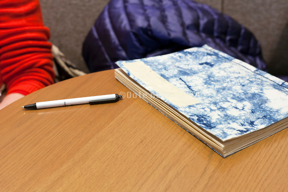 notebook with pen laying on a table