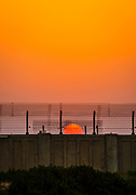 Orange Sunset over a security wall of concrete and barbed wire Photographed in Israel