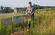 Len Uecker retired with his wife and settled down on the shore of Greer Ferry Lake in Quitman. Arkansas in the Fayetteville Shale region.  He stands next to a warning sign at a frack site less then a mile from his home. When fracking started in the area hw started an NGO to save the lake.