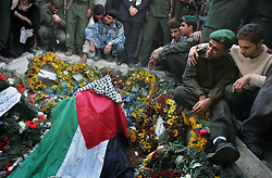 Palestinian security officers and mourners gather around the grave of Palestinian leader Yasser Arafat after the funeral at his compound, Ramallah, Palestinian Territories, Nov. 12, 2004. Arafat died in a Paris hospital at the age of 75.