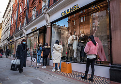 © Licensed to London News Pictures. 04/11/2020. London, UK. Shoppers queue up at Chanel in Chelsea. Last minute shopping on the King's Road in Chelsea, London with only a few hours left before another National lockdown begins. Prime Minister Boris Johnson announced last Saturday a new Covid-19 lockdown restrictions for England from Thursday (tomorrow) with pubs, restaurants, non-essential shops and gyms to close. The Prime Minister also warned MPs that deaths from Covid-19's second wave could be twice as high as the first ahead of MPs voting on the Government's 4 week lockdown measures today. Photo credit: Alex Lentati/LNP