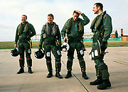 Four RAF fighter pilots of the 'Red Arrows', Britain's Royal Air Force aerobatic team stand on their home airfield at RAF Scampton after another hard day of winter training sorties (flights). The four swap banter with others before a post-flight debrief. Holding their helmets and wearing heavy boots, anti-g-pants and life vests these men form an elite squadron with the RAF but have accumulated over 1,500 flying hours in fast jets with experience in theatres of war. After three years in the Red Arrows they return to frontline and instructing duties. Since 1965 the squadron have flown over 4,000 shows in 52 countries. During a forthcoming calendar of appearances at air shows and fly-pasts across the UK and a few European venues they are an important recruiting tool for future personnel – of pilots and ground-based trades.