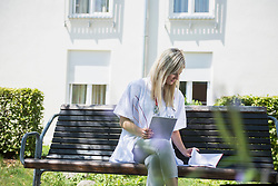 Female doctor working on a bench in the garden with digital tablet and notes, Bavaria, Germany, Europe