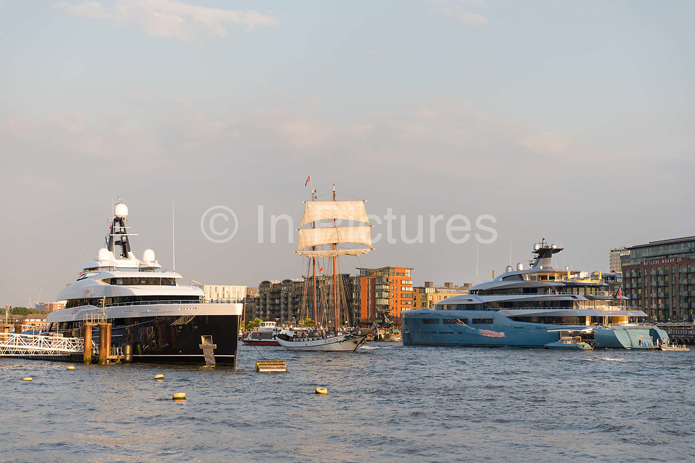 A tall ship sails past the brand new 74.5m long superyacht, Elandess, seen moored at HMS President on the River Thames on July 05, 2018 after making its maiden voyage to London this week and pictured here opposite the Aviva superyacht which arrived last week. Elandess was built at the Abeking and Rasmussen shipyard in Germany for owner, Lloyd Dorfman, the founder of Travelex, was launched in May 2018 and has just completed sea trials ahead of its London visit. Elandess has an axe-bow, dark hull and low-slung superstructure. There are a variety of entertaining communal spaces, from the 8 x 2.5-metre superyacht swimming poollocated on the massive sun deckto the Nemo Loungewith portholesbelow the waterline and an observation lounge on the upper deck. Guest accommodation includes six staterooms, including the master suitewhich is placed forward on the main deck with an observation lounge directly above on the upper deck.