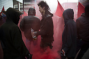 Anarchists gather as a black bloc letting off smoke bombs for the Fuck Parade to party and protest at the class and wealth divide between rich and poor and the gentrification of London, the demonstration was organised by anarchist group Class War on May 1st 2016 in London, United Kingdom. The parade is now part of the May Day activism calendar as dissatisfaction about the establishment, the police and the inadequacy of the press is highlighted.