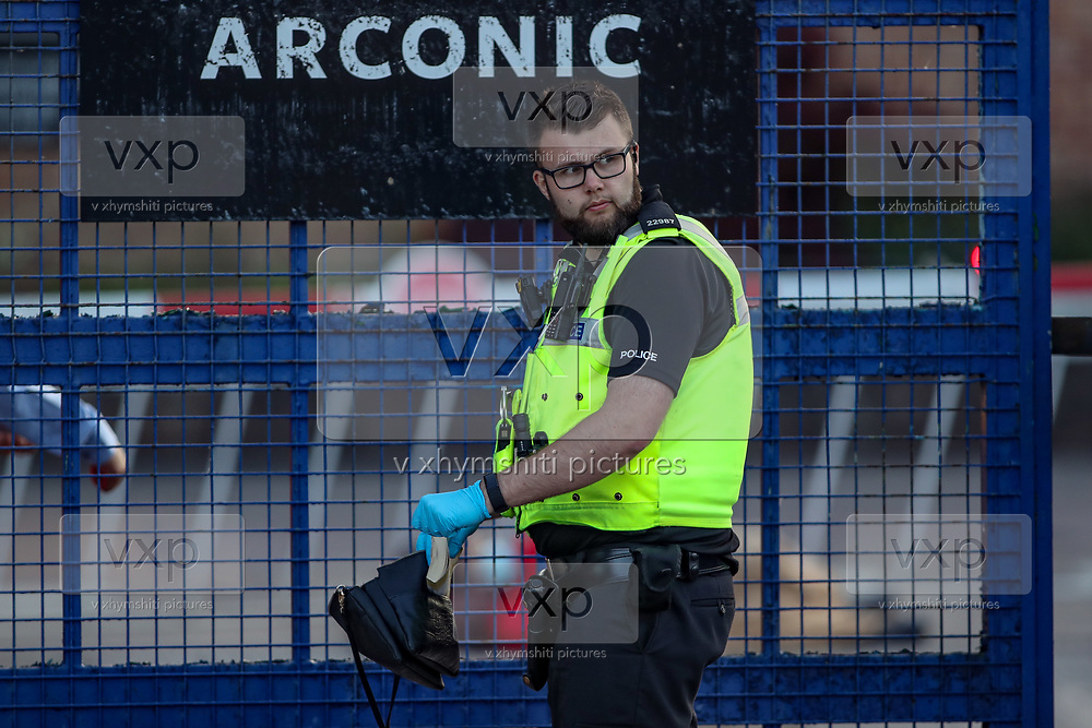 Birmingham, United Kingdom, June 14, 2021: A police officer of West Midlands police appears to be searching on the personal belongings of one of the Palestine Action activists who chained themselves outside the entry gates of Arconic admin offices on Monday, June 14, 2021. Arconic is an American industrial company specializing in lightweight metals engineering and manufacturing known as Arconic in Bermingham on Monday, June 14, 2021.  (Photo by Vudi Xhymshiti)