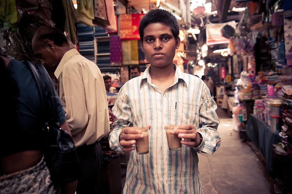 A young boy delivers tea at INA market New Delhi