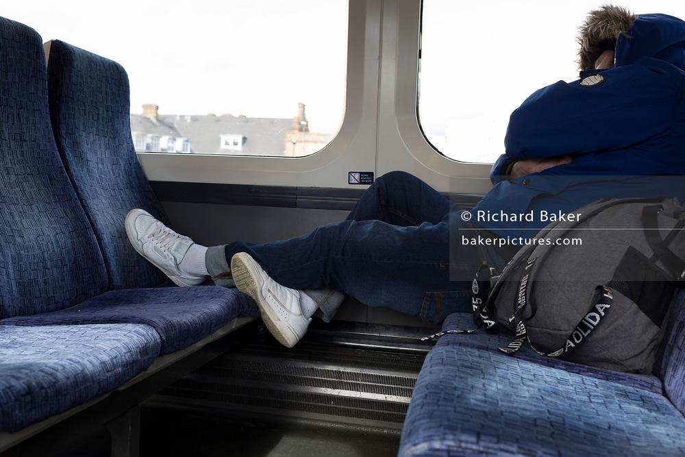 The white trainer shoes of a sleeping rail passenger are on a train carriage seating during a commuter journey across south London into Victoria station, on 11th March 2020, in London, England.