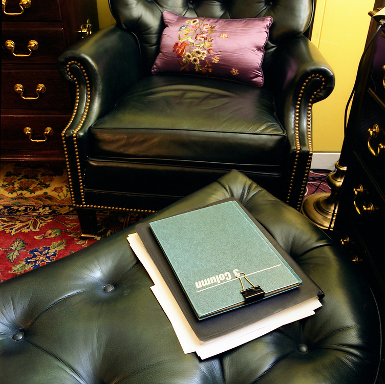 Looking down and across an ottoman towards a chair and a purple rectangular pillow on it. There is a datebook of some sort on the ottoman.