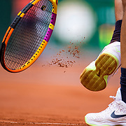 PARIS, FRANCE June 9.  Rafael Nadal of Spain hits the soles of his tennis shoes with his racquet to clean the clay off while serving against Diego Schwartzman of Argentina on Court Philippe-Chatrier during the quarter finals of the singles competition at the 2021 French Open Tennis Tournament at Roland Garros on June 9th 2021 in Paris, France. (Photo by Tim Clayton/Corbis via Getty Images)