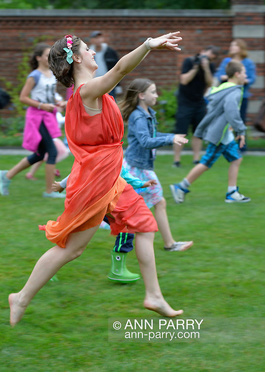 Old Westbury, New York, USA. 28th June 2015. Lori Belilove & The Isadora Duncan Dance Company, dressed in Renaissance themed tunics, give dancing lessons to children throughout the gardens, and then perform at historic Old Westbury Gardens, a Long Island Gold Coast estate, for its Midsummer Night event. A member of the dance company in an orange tunic is shown dancing with the children.