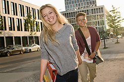 Portrait of teenage couple coming from school, smiling
