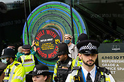 Police form a blockade around Extinction Rebellion activists at a staged event claiming Naples Group conducts business using blood money on 27th August, 2021 in London, United Kingdom. The activist group Extinction Rebellion XR are planning actions of disruption for two weeks straight beginning on August 23rd, 2021 in an effort to bring awareness and priority to the global climate emergency in advance of the COP 26 Summit which will be held in Glasgow later this year.