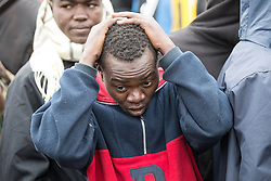 © Licensed to London News Pictures . 24/10/2016 . Calais , France . A crying man in the queue to leave the Jungle migrant camp in Calais , Northern France , on the day of a planned eviction and start of the destruction of the camp . Photo credit: Joel Goodman/LNP