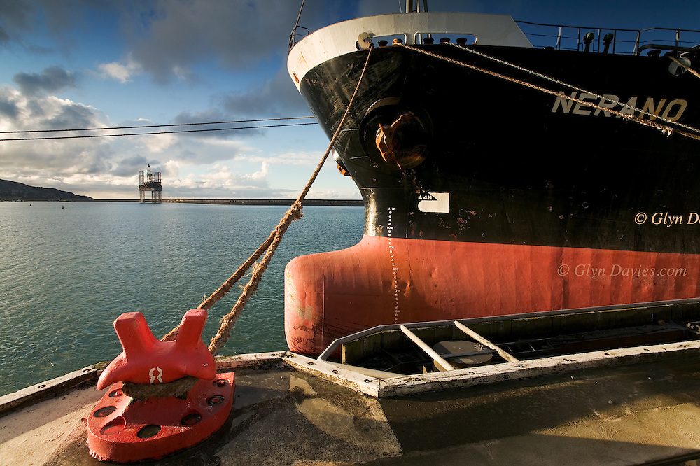A Malaysian bulk carrier is moored up alongside the Anglesey Aluminium Wharf in Holyhead Harbour. This shot was taken from the very top deck above the bridge, looking towards an oil rig in for repairs. The huge breakwater in the background is what makes this such a well protected harbour.