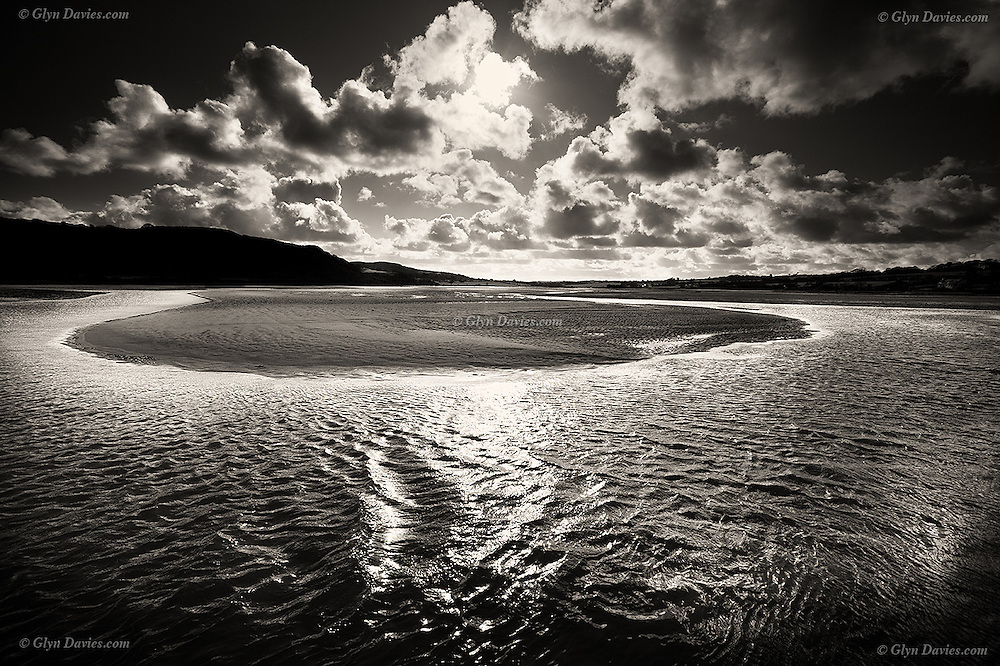 Sunset and clouds over water channels exposed at low tide in the Dulas Estuary, Anglesey, North Wales