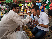 31 AUGUST 2014 - SARIKA, NAKHON NAYOK, THAILAND: A Thai is a annointed by a Hindu priest at the Ganesh festival at Shri Utthayan Ganesha Temple in Sarika, Nakhon Nayok. Ganesh Chaturthi, also known as Vinayaka Chaturthi, is a Hindu festival dedicated to Lord Ganesh. It is a 10-day festival marking the birthday of Ganesh, who is widely worshiped for his auspicious beginnings. Ganesh is the patron of arts and sciences, the deity of intellect and wisdom -- identified by his elephant head. The holiday is celebrated for 10 days, in 2014, most Hindu temples will submerge their Ganesh shrines and deities on September 7. Wat Utthaya Ganesh in Nakhon Nayok province, is a Buddhist temple that venerates Ganesh, who is popular with Thai Buddhists. The temple draws both Buddhists and Hindus and celebrates the Ganesh holiday a week ahead of most other places.    PHOTO BY JACK KURTZ