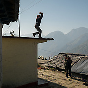 A boy dances on top of a roof.