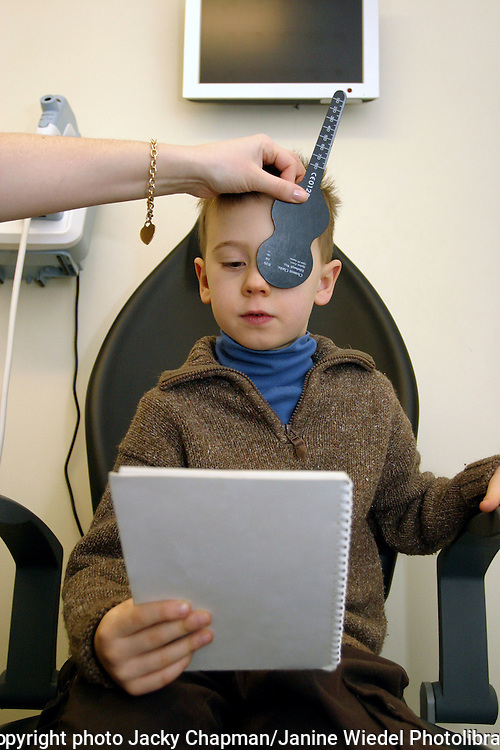 Young child having his eyes tested at opticians