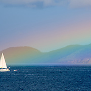 A sailing boat cruises by the base of a rainbow in the US Virgin Islands in the Caribbean.