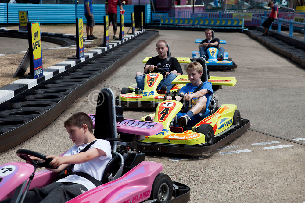 Boys race the go karts at Adventure Island Funfair at Southend-on-sea, Essex. The town could be described as run down as while there are some signs of affluence, these are few and far between. The predominant atmosphere is quite rough feeling and quite poor. Southend is a seaside resort that is very popular with people from the East side of London due to it's close proximity, just an hour away by train along the Thames Gateway. With the decline of seaside resorts, from the 1960s much of the centre was developed for commerce and many of the original features were destroyed through redevelopment or neglect.