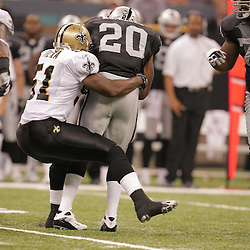 2008 October, 12: New Orleans Saints linebacker Jonathan Vilma (51) tackles Oakland Raiders running back Darren McFadden (20) during a week six regular season game between the Oakland Raiders and the New Orleans Saints at the Louisiana Superdome in New Orleans, LA.