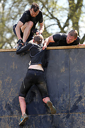 "©Licensed to London News Pictures. 13/05/2012.Boughton House, Northants. Tough Mudders helping another competitor over ""Everest"" at the end of 12 mile endurance challenge..Photo credit: Steven Prouse/ LNP"