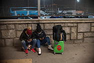 Two Sub-saharan  migrants wait for the night bus that would take them to France. Irun (Basque Country). March 11, 2021. As the number of migrants arriving on the coasts of southern Spain incresead, more and more migrants are heading north to the border city of Irun on their way to reach France, Belgium or other European countries, but the controls of the French police make it difficult for them to pass. (Gari Garaialde / Bostok Photo)