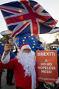 As Prime Minister Theresa May tours European capitals hoping to persuade foreign leaders to accept a new Brexit deal following her cancellation of a Parliamentary vote, a pro-EU Santa rings a Brexit bell during a protest opposite the Houses of Parliament, on 11th December 2018, in London, England.