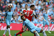 Sergio Aguero of Manchester city is challenged by Alex Oxlade-Chamberlain of Arsenal.   The Emirates FA Cup semi-final match, Arsenal v Manchester city at Wembley Stadium in London on Sunday 23rd April 2017.<br /> pic by Andrew Orchard,  Andrew Orchard sports photography.