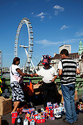 Tourists buy cheap souvenirs on Westminster bridge by the River Thames at Westminter, London. With the iconic London Eye behind this is one of the busiest areas for tourism in the city.