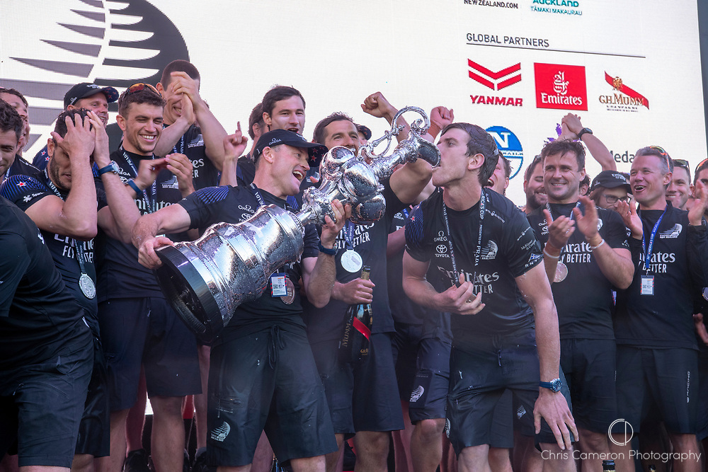 Emirates Team New Zealand celebrate on stage after being presented with the Americas Cup on stage after beating Luna Rossa Prada Pirelli Team 7 - 3. Glen Ashby pours for Peter Burling.  Wednesday the 17th of March 2021. Copyright photo: Chris Cameron