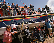 RNLI spectators watch the Red Arrows, Britain's RAF aerobatic team displaying high above their heads during public airshow.