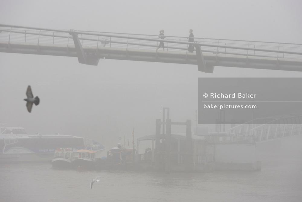 Morning fog envelopes pedestrians crossing the river Thames on the Millennium Bridge.