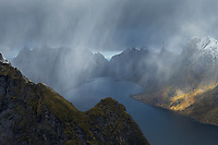 Autumn snow flurries fall over mountain peaks with view towards Kirkefjord from Reinebringen mountain peak, Moskenesøy, Lofoten Islands, Norway