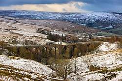 © Licensed to London News Pictures. 04/01/2021. Stone House UK. A commuter train passes through a winter scene as it crosses dent head viaduct near Stone House this morning in the Yorkshire Dales. Photo credit: Andrew McCaren/LNP