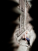 A local guide waits for his tour group in Angkor Wat at Angkor, Siem Reap Province, Cambodia