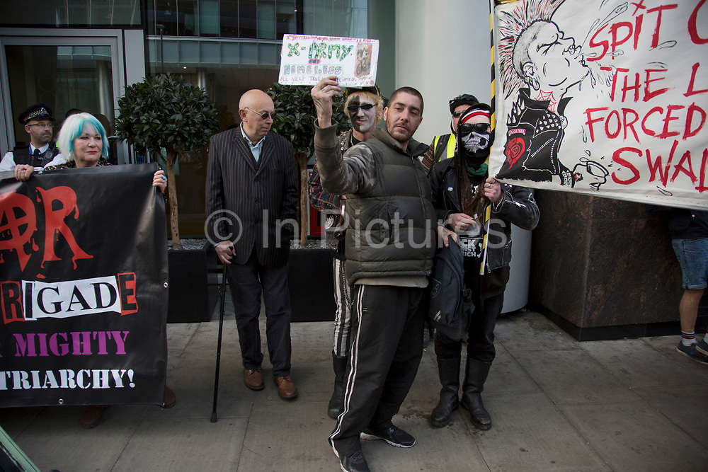 Anarchists gather as a black bloc for the Fuck Parade to party and protest at the class and wealth divide between rich and poor and the gentrification of London, the demonstration was organised by anarchist group Class War on May 1st 2016 in London, United Kingdom. The parade is now part of the May Day activism calendar as dissatisfaction about the establishment, the police and the inadequacy of the press is highlighted. Ian Bone publisher of anarchist newspaper Class War seen here with protesters. He has been involved in social campaigns since the 1960s.
